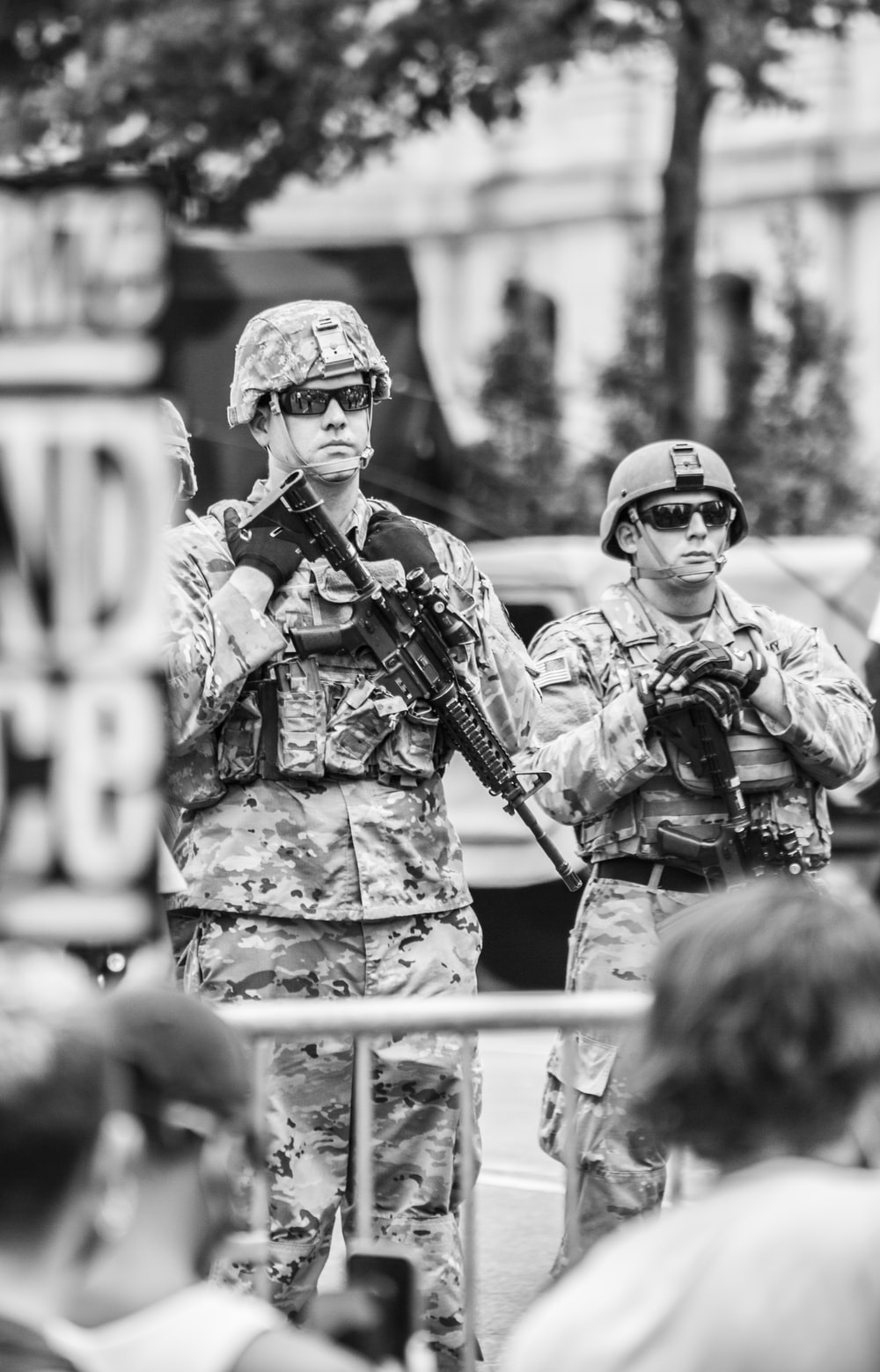 grayscale photo of man in camouflage uniform holding rifle