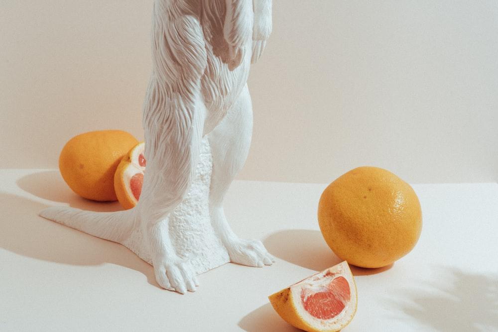 white angel figurine beside orange fruit