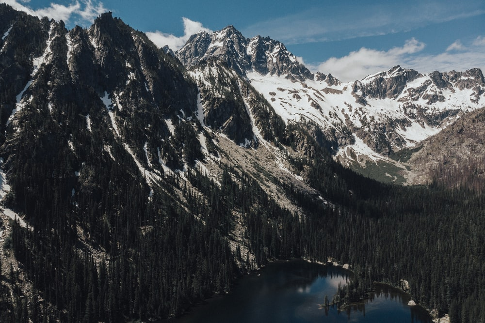 snow covered mountain near lake during daytime