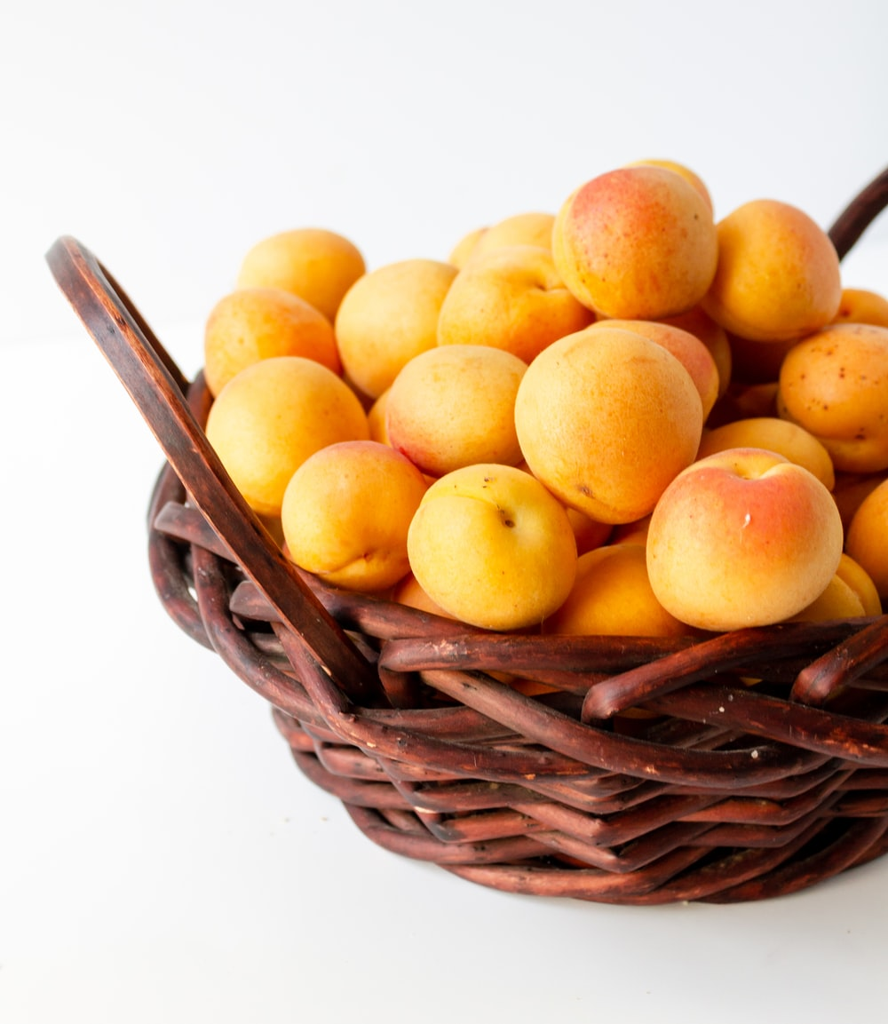 yellow round fruits on brown woven basket