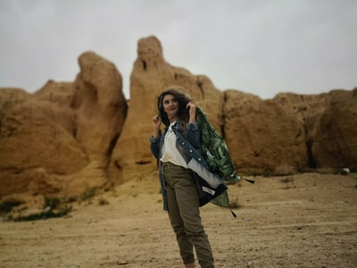 man and woman standing on brown rock formation during daytime iranian teams background