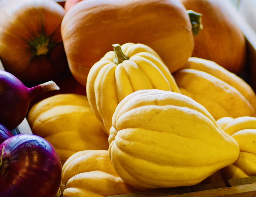 yellow and red squash on brown wooden table