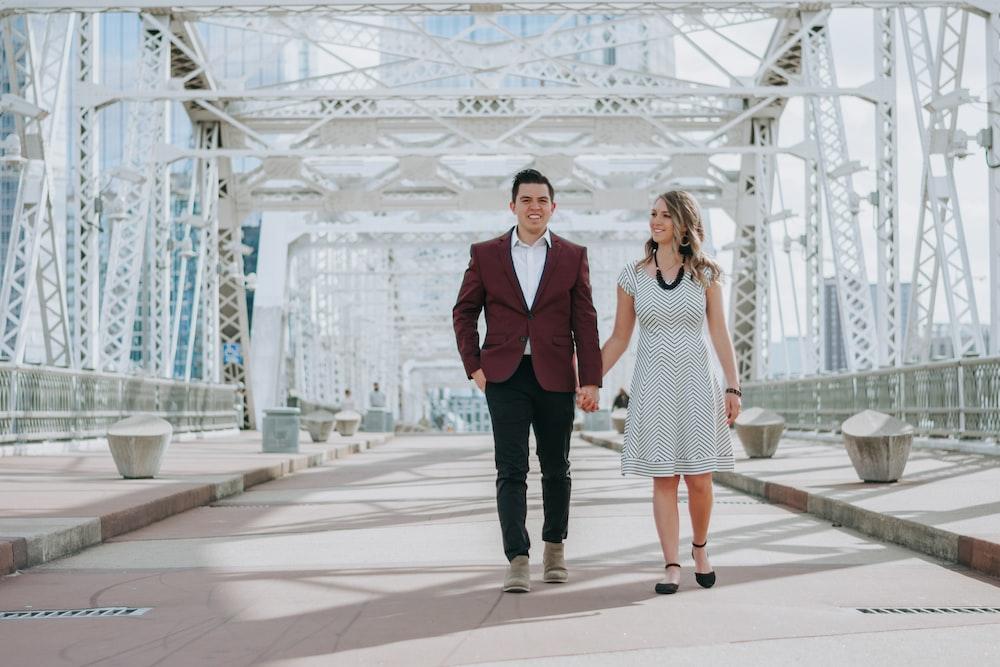 man in black suit jacket standing beside woman in white dress