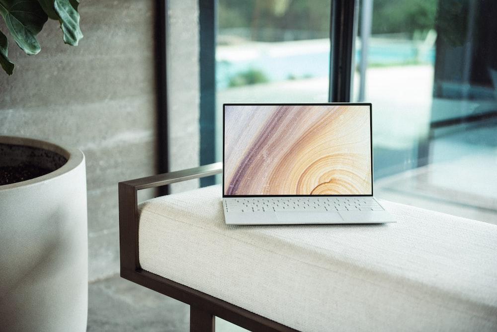 茶色の木製テーブルの上の銀のラップトップ