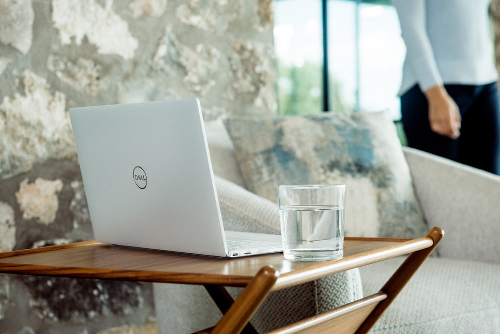 silver laptop on brown wooden table