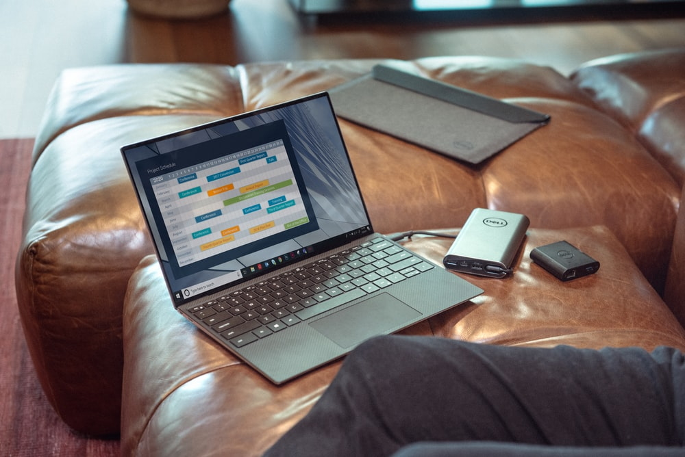 black and gray laptop computer on brown leather couch
