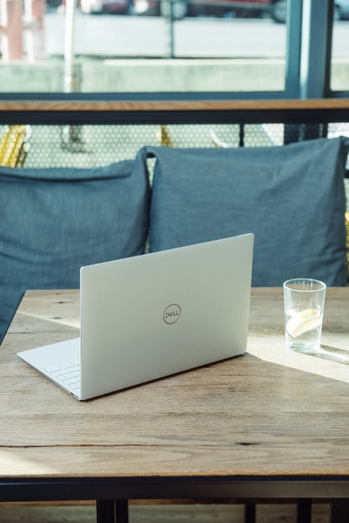 Description: man using laptop in front of brown chair