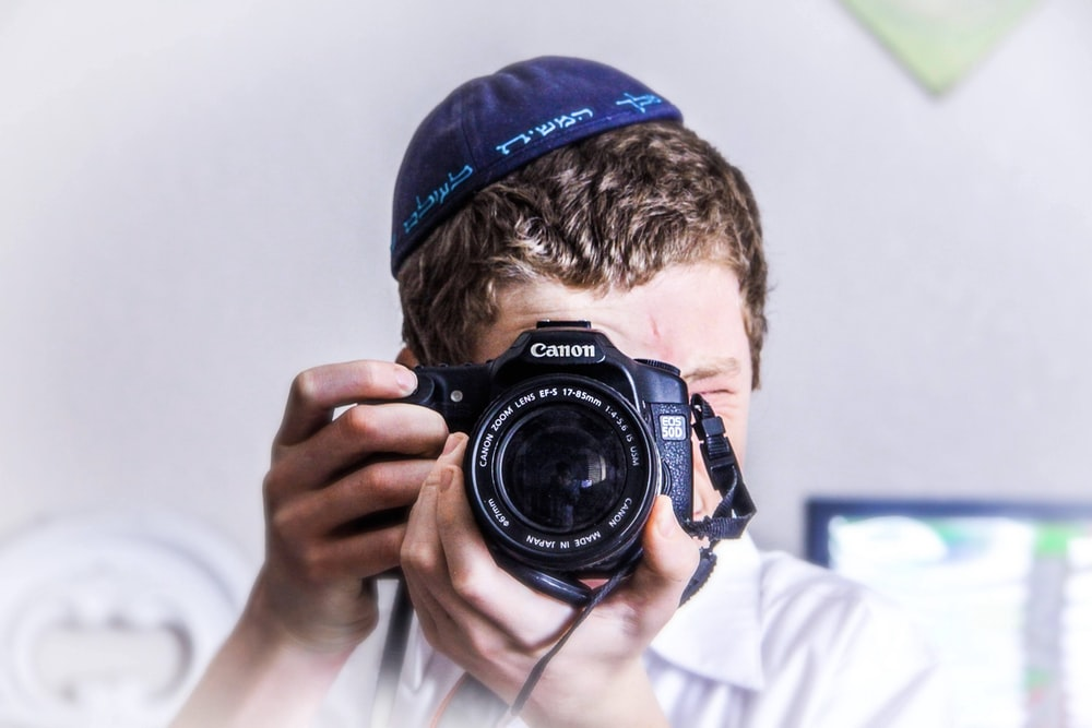 man in blue knit cap holding black and silver nikon dslr camera
