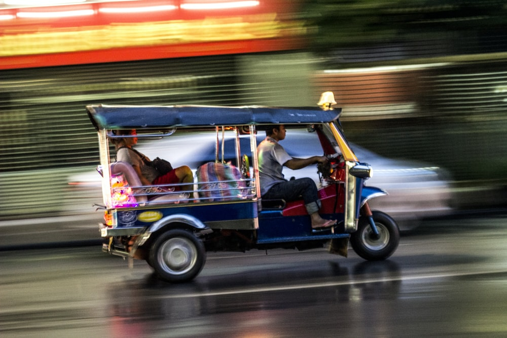 2 men riding on red and blue auto rickshaw