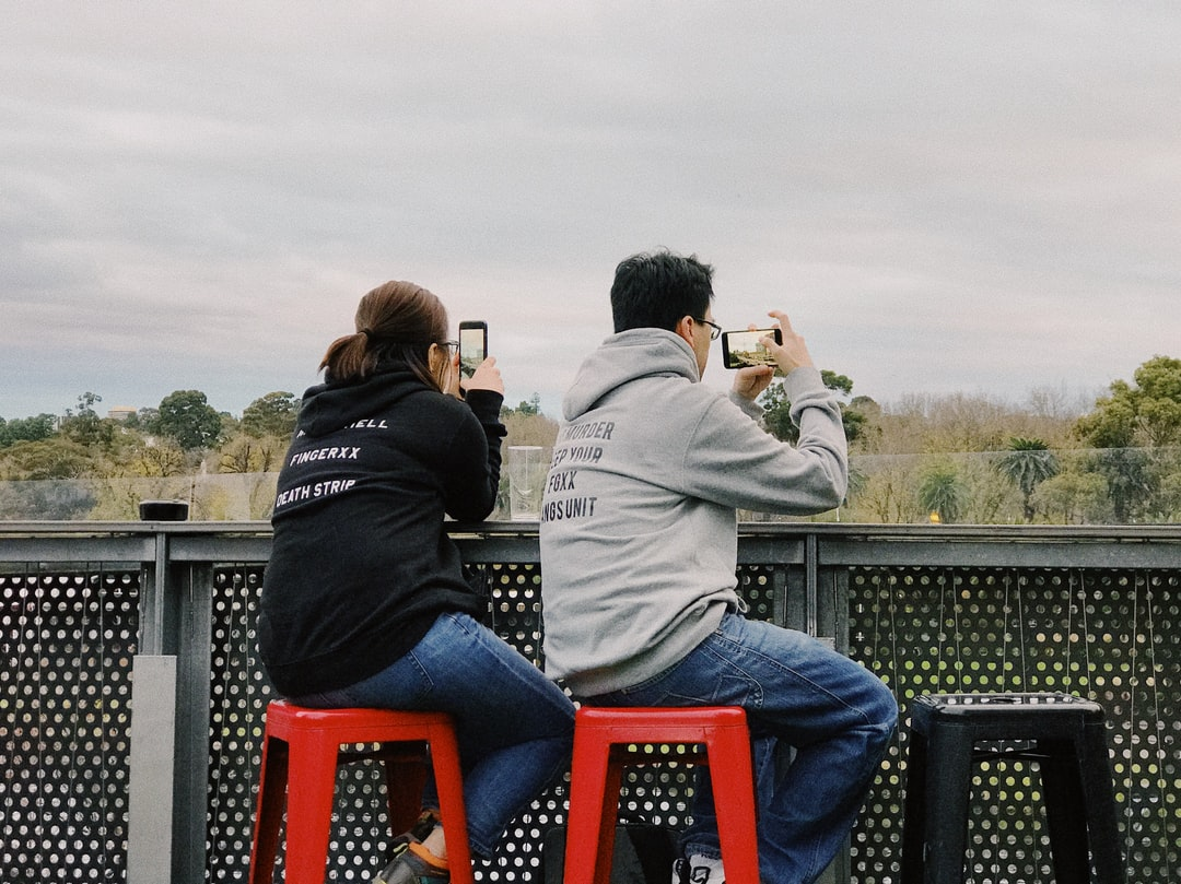 A couple taking photos of scenery on their iPhones/smartphones. One holds the phone in portrait orientation, the other in landscape orientation. This image is ideal for stories about the use of phones, technology, and social media in modern life, or photography habits with Instagram. Both people are Asian, and are wearing jeans and hoodies. They are sitting on red barstools and their body positions mirror each other. The shot is taken from behind them, and is composed with the subjects in the center. The colors are slightly muted with faded highlights, but the red stools are saturated and pop.