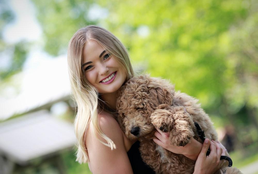 woman in black tank top hugging brown long coated dog
