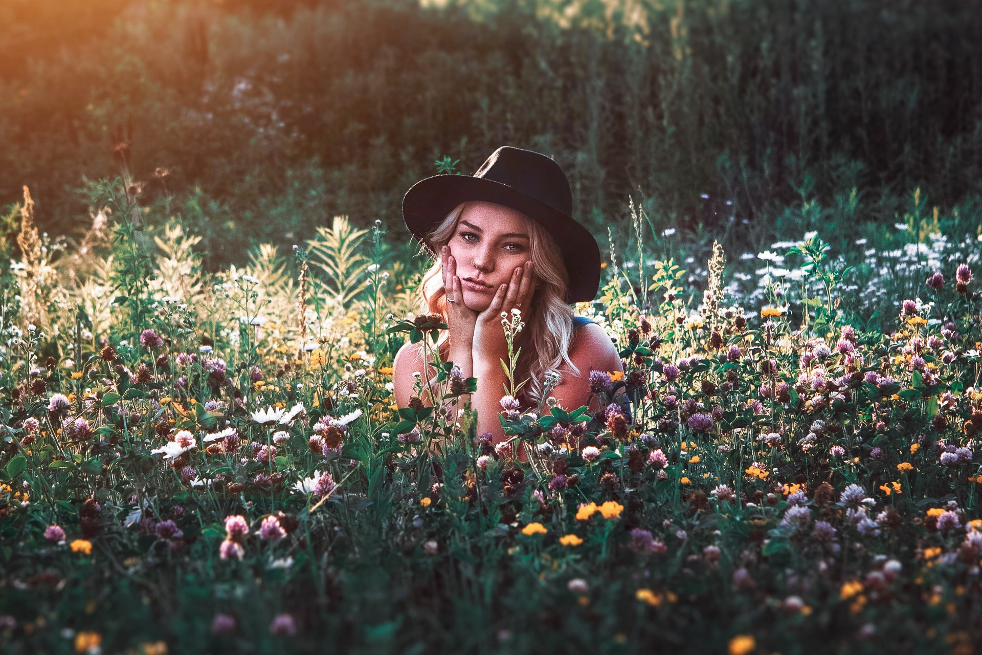 woman in black hat on flower field during daytime