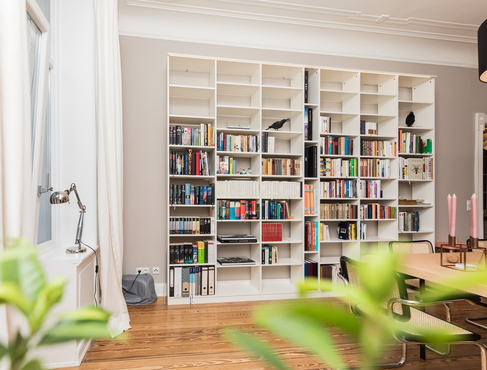 white wooden book shelves on brown wooden parquet floor