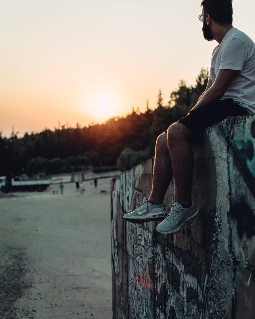 man in white t-shirt sitting on concrete fence during sunset
