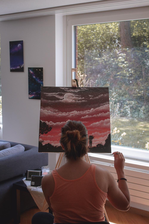 woman in pink tank top standing near window
