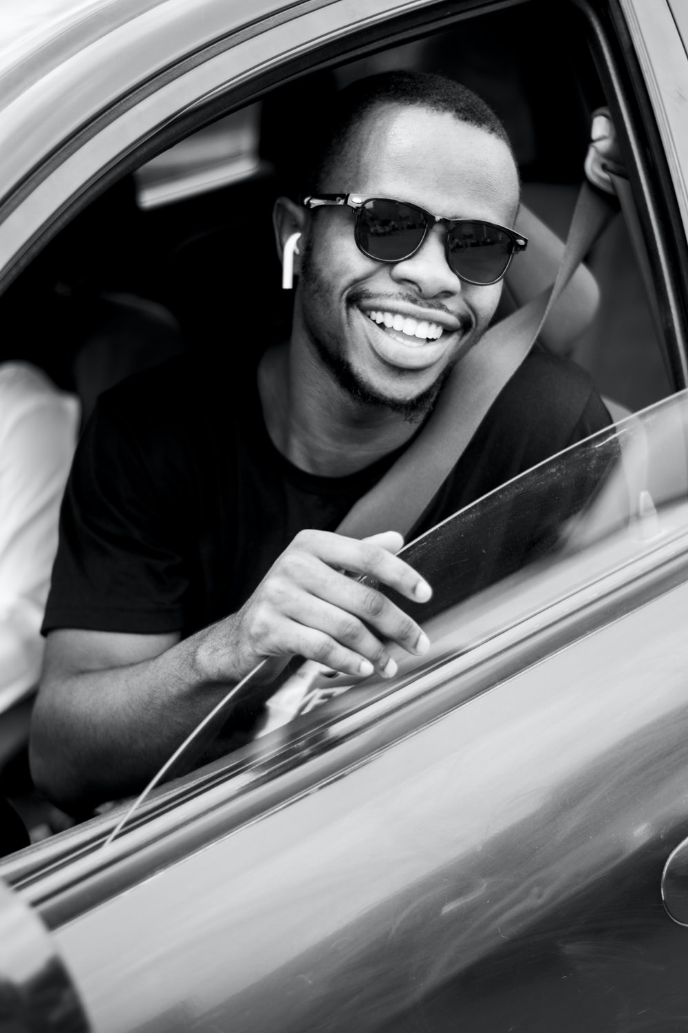 grayscale photo of man wearing sunglasses driving car