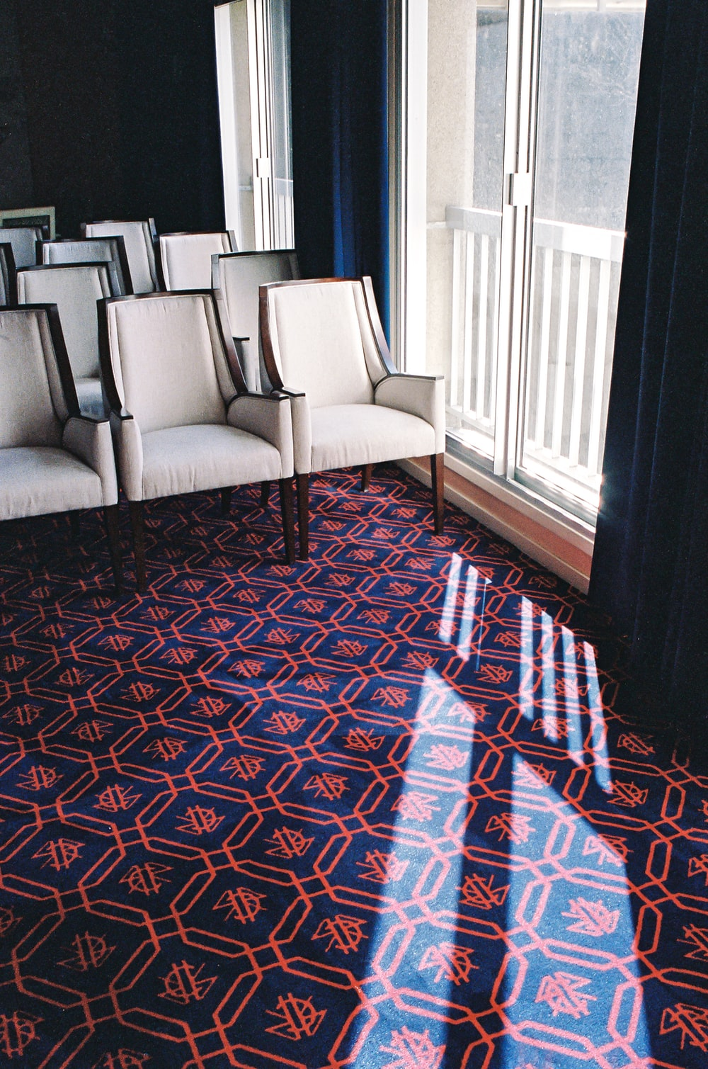 white leather sofa chair on red and blue area rug