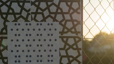 Graphic poster on wire mesh fence.