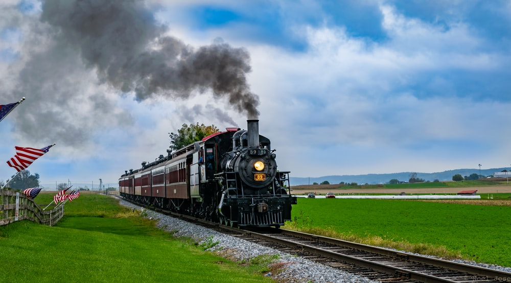 black and red train on rail tracks under white clouds and blue sky during daytime