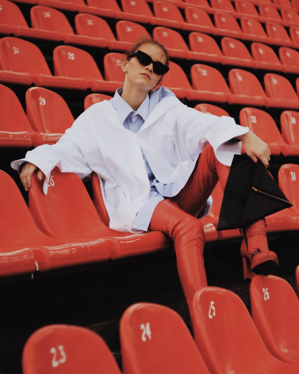 man in white dress shirt and red pants sitting on red chair
