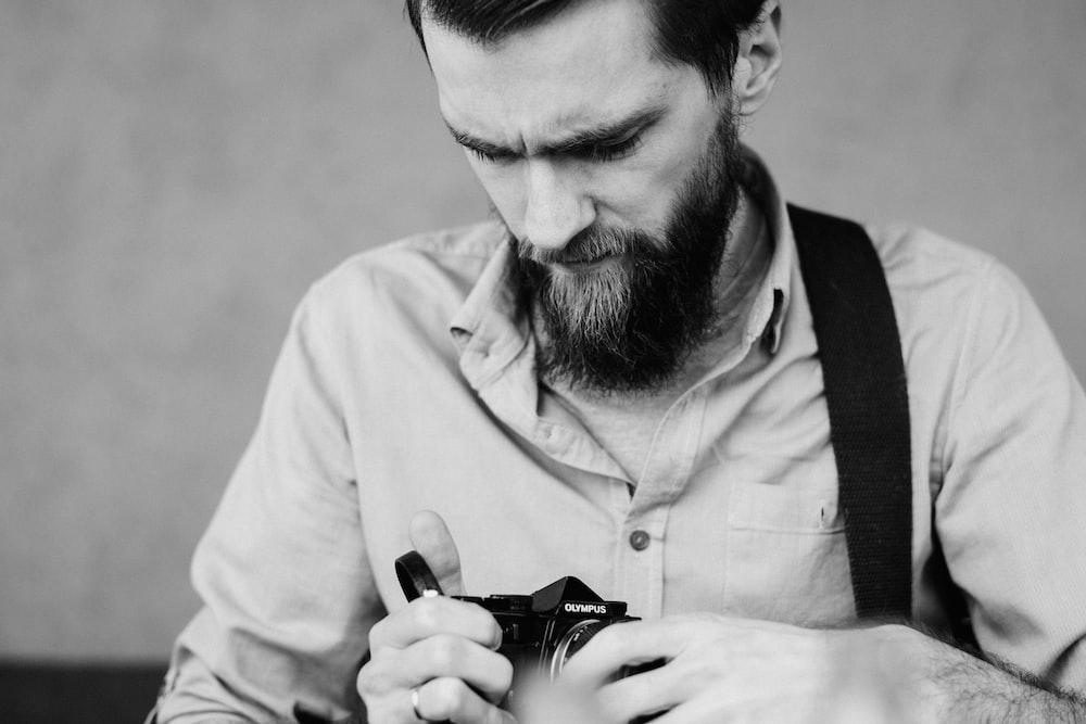 man in white dress shirt holding black dslr camera