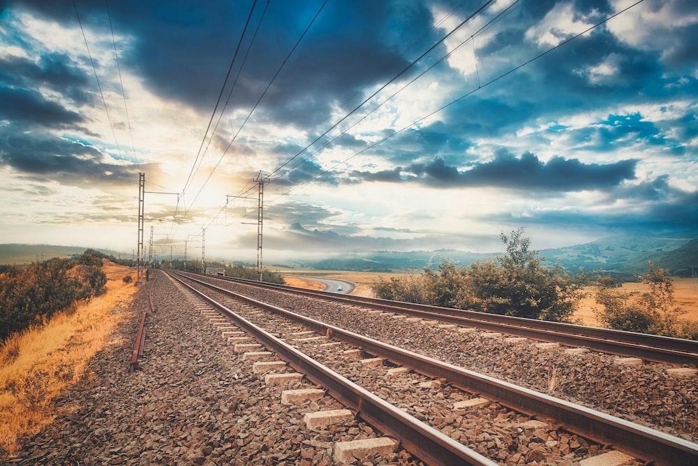 brown train rail under blue sky during daytime