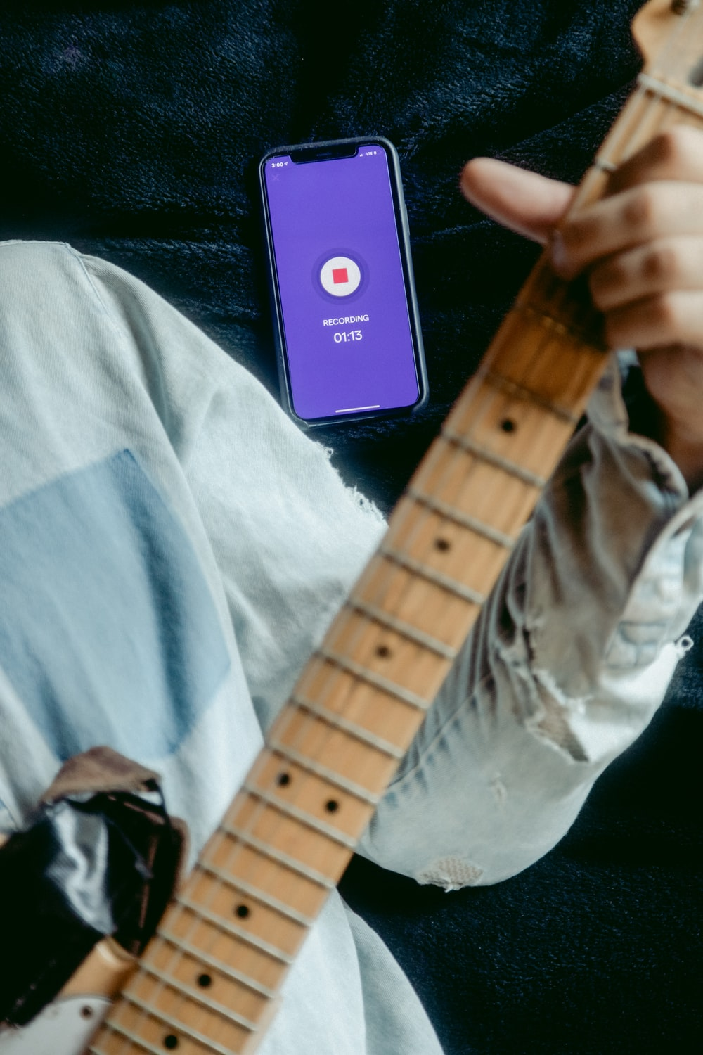 person holding brown electric guitar