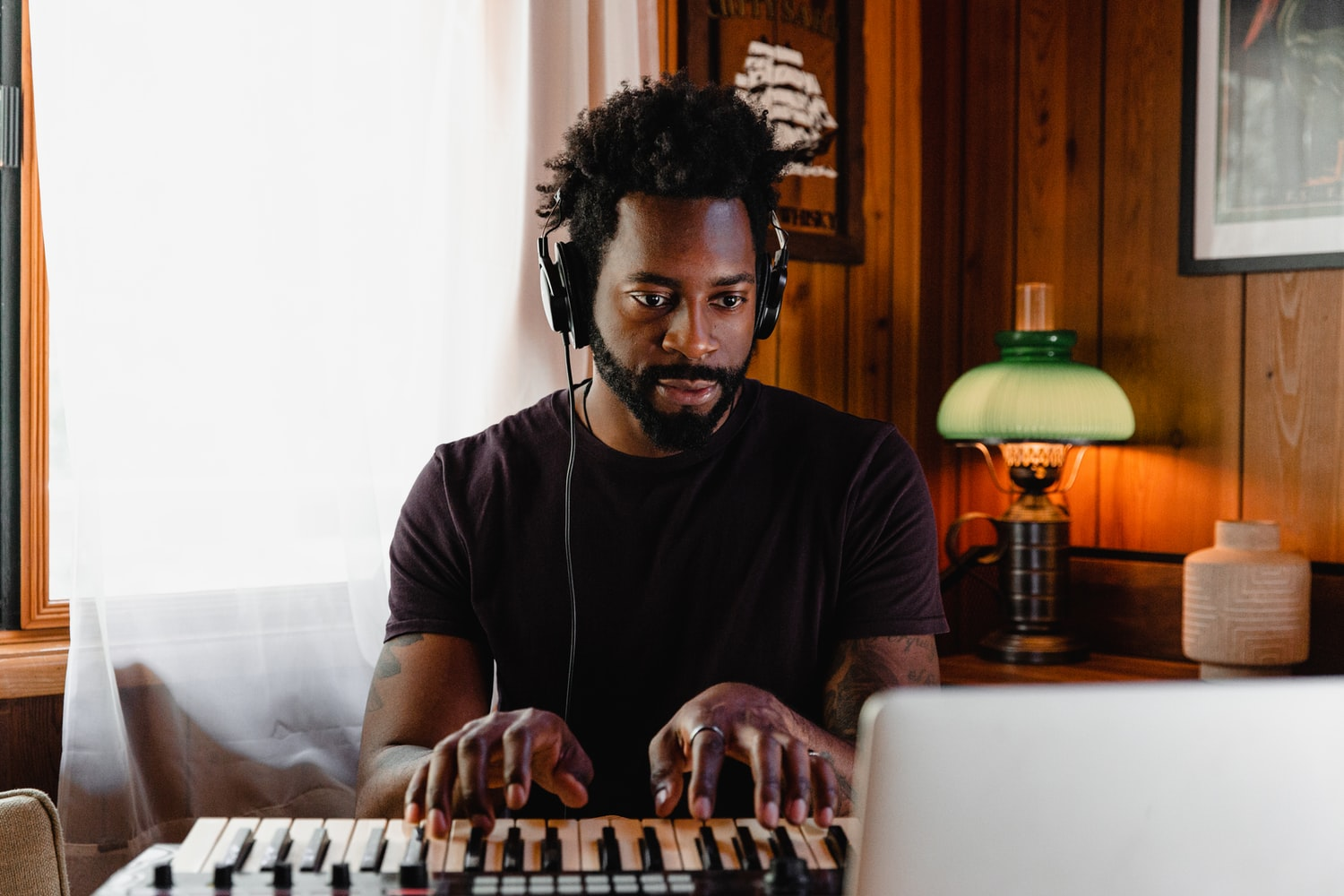 Man with headphones playing keyboard in front of computer.