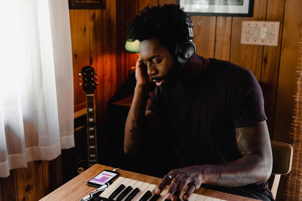 man in black crew neck t-shirt wearing headphones