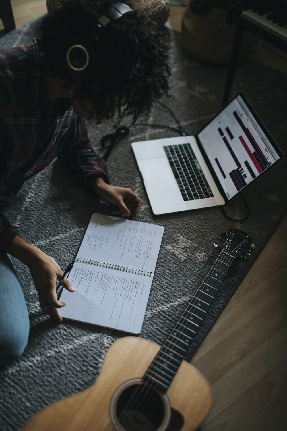 person in black jacket sitting on floor while writing on notebook