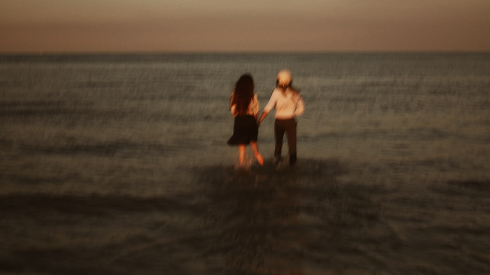 2 women standing on beach during sunset