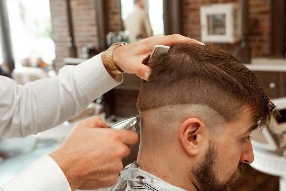 man in white dress shirt cutting hair of man
