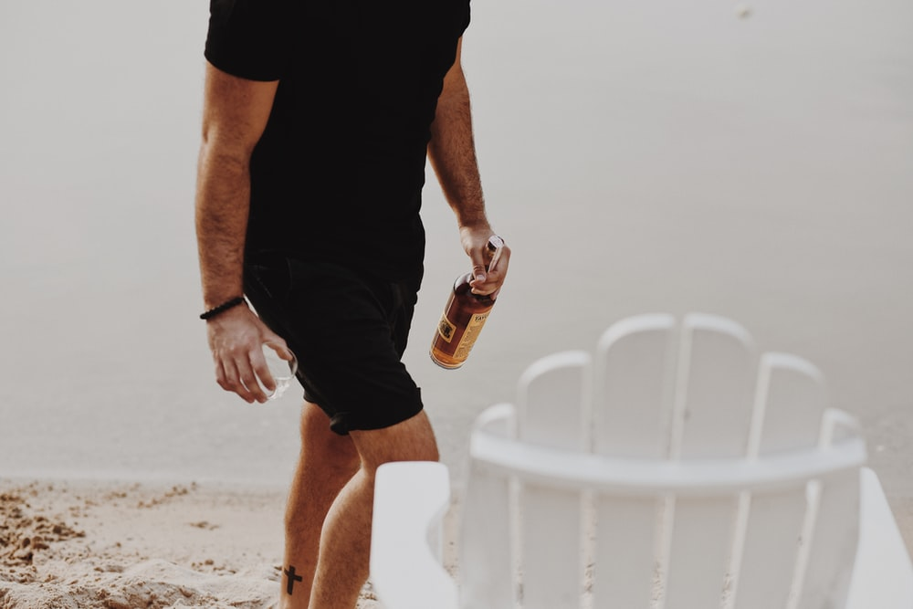 man in black t-shirt and black shorts holding bottle