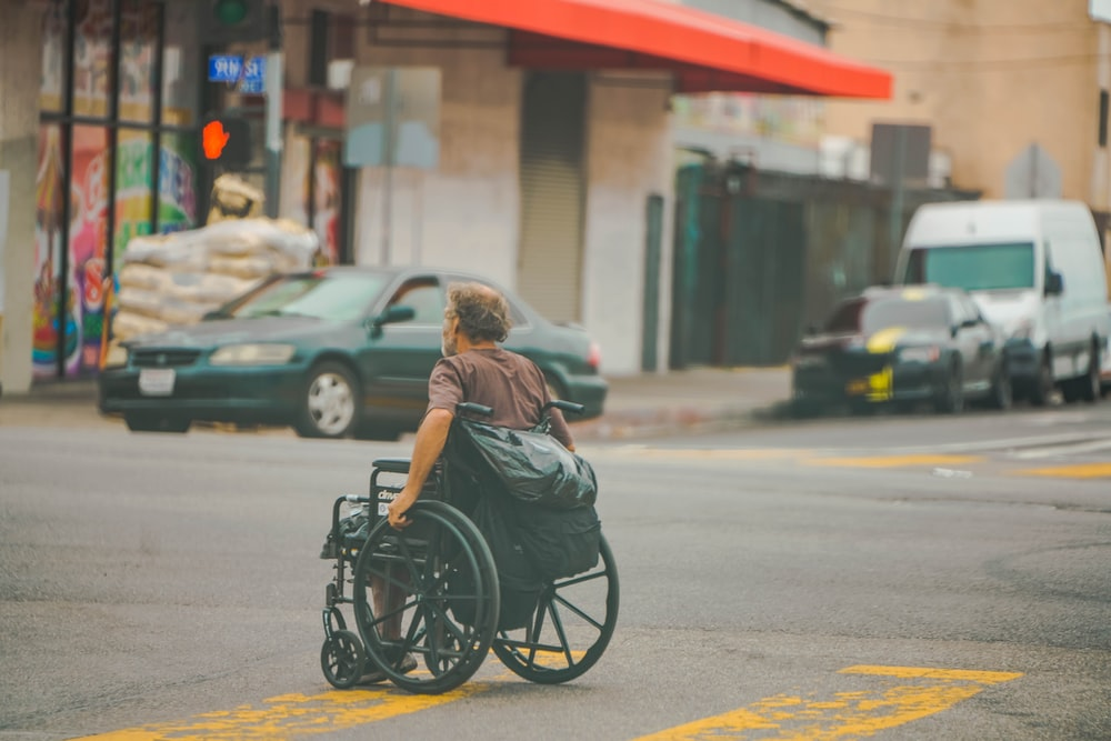 woman in gray shirt sitting on black wheelchair on road during daytime