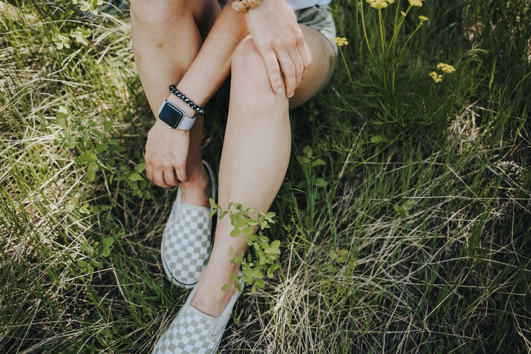 Woman In White and Black Checkered Dress Shirt and White Pants Sitting On Green Grass Field - unsplash