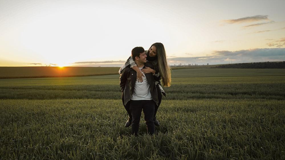2 women standing on green grass field during sunset