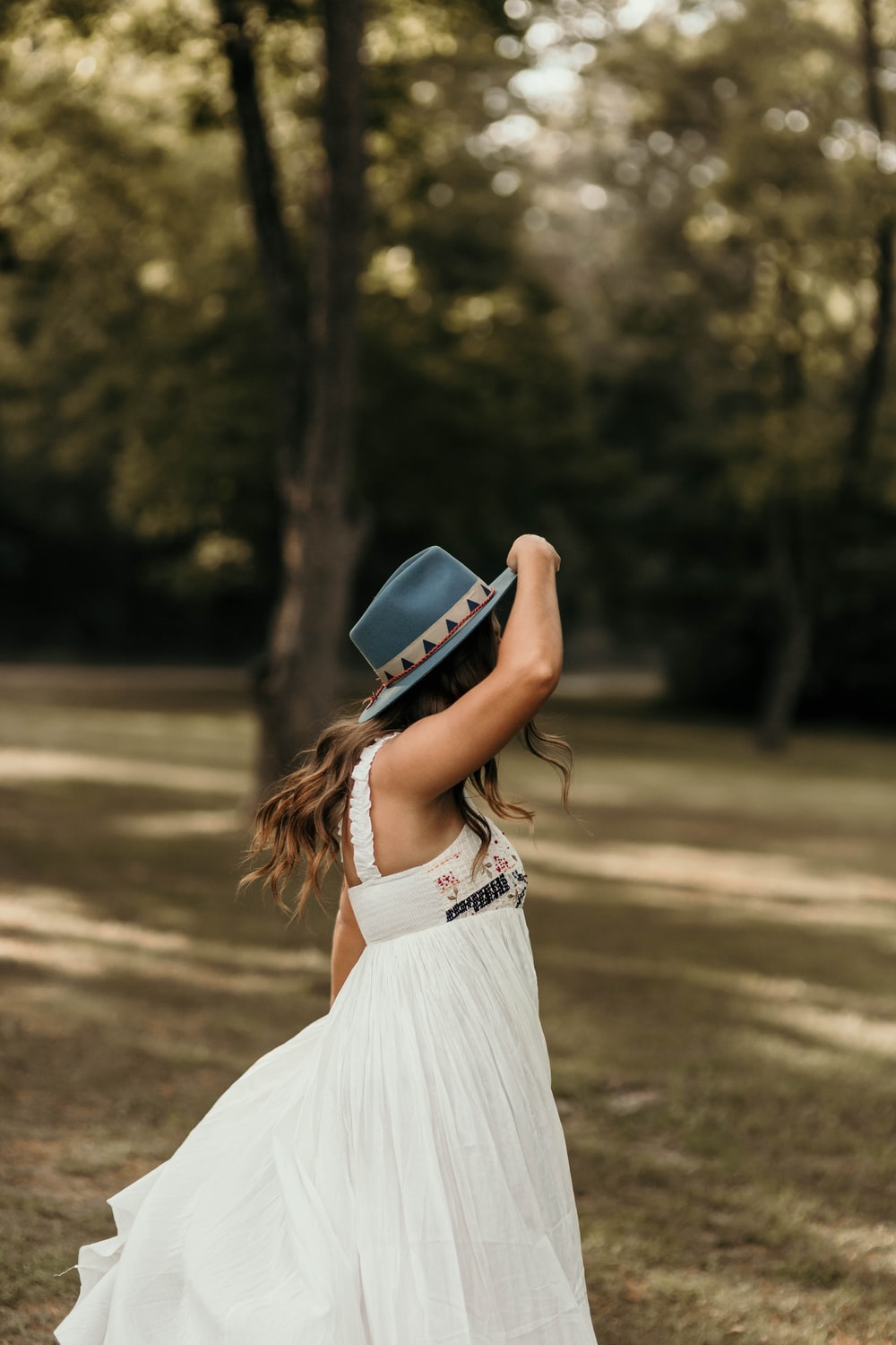 woman in white dress wearing blue fedora hat standing on brown field during daytime