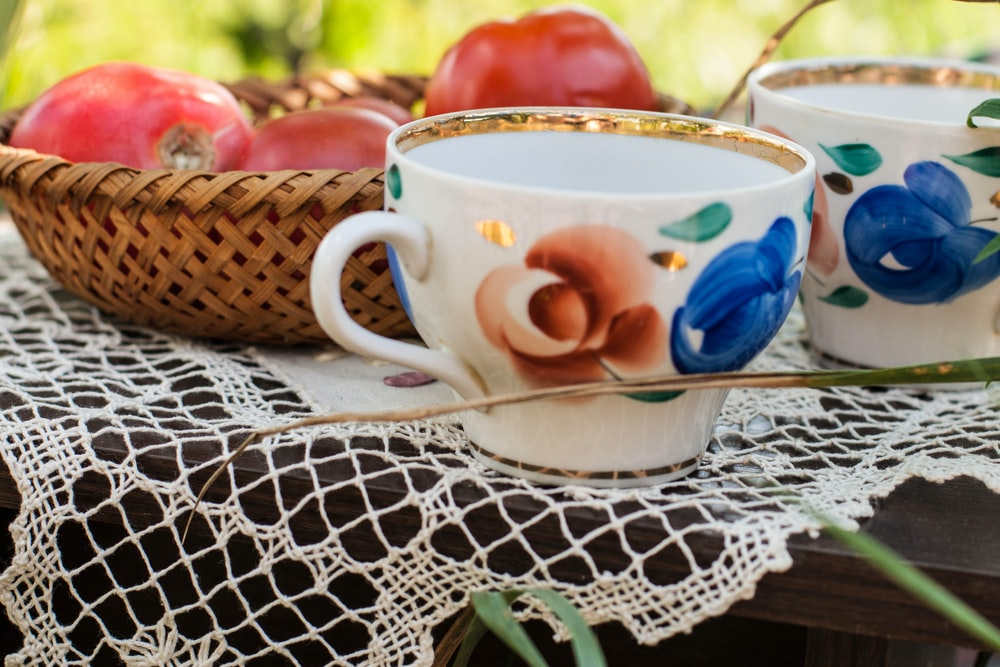 white and pink floral ceramic teacup on white and blue floral table cloth