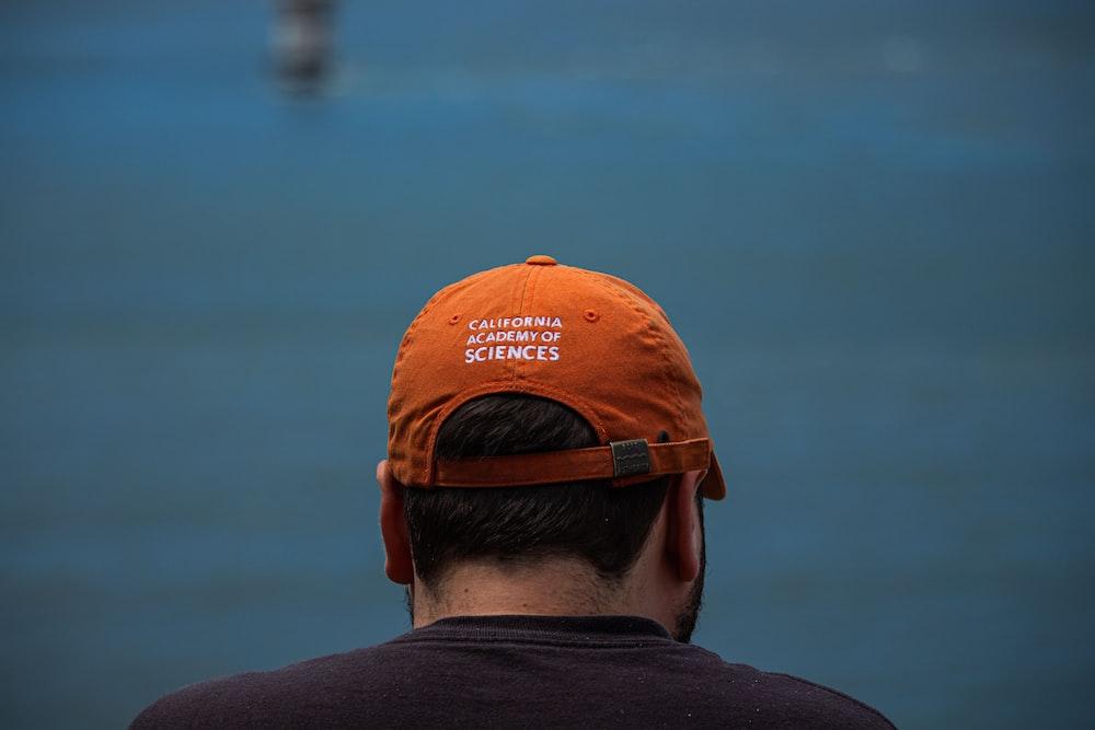 man in orange and white cap and black shirt