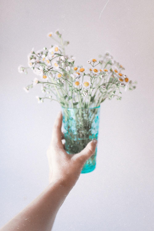 white flowers in blue glass vase