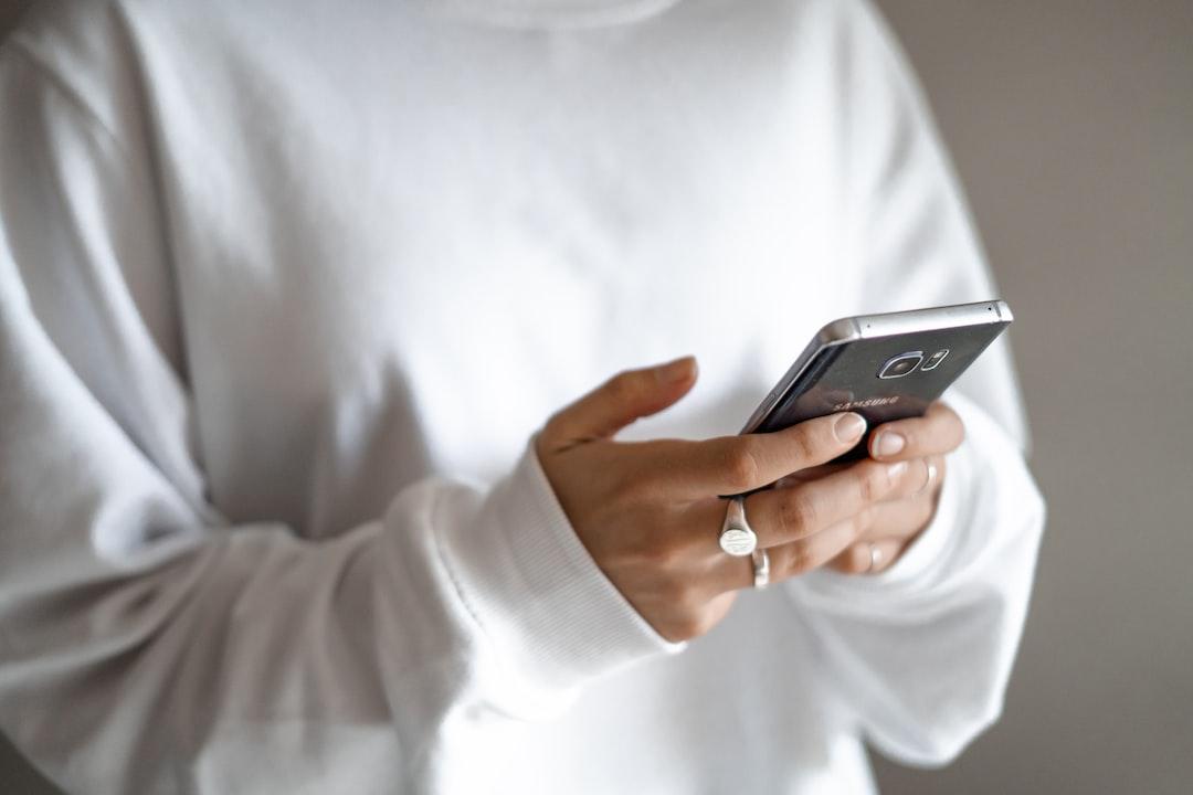 Girl Holding Phone Wearing White Jumper - unsplash