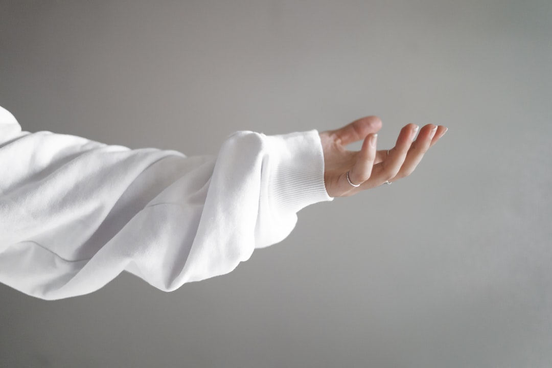 Girl Hand Facing Up Wearing White Jumper - unsplash
