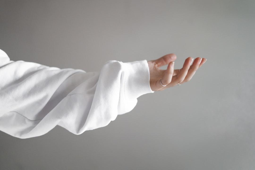 Girl Hand Facing Up Wearing White Jumper - unsplash