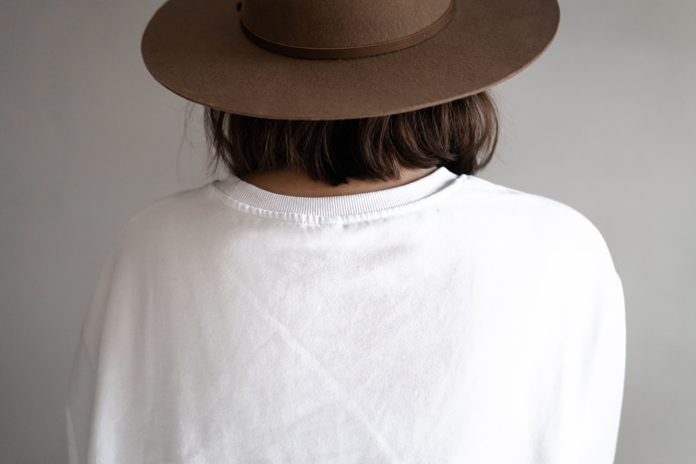 person in white crew neck shirt wearing brown fedora hat
