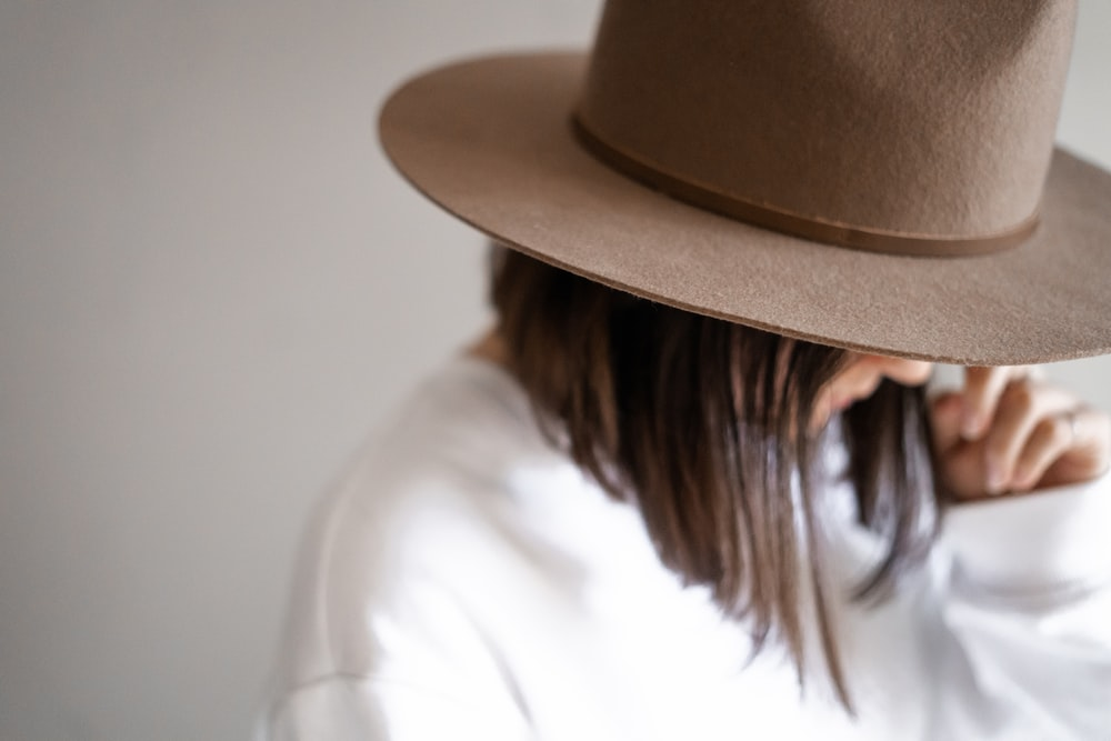 woman in white shirt wearing brown fedora hat