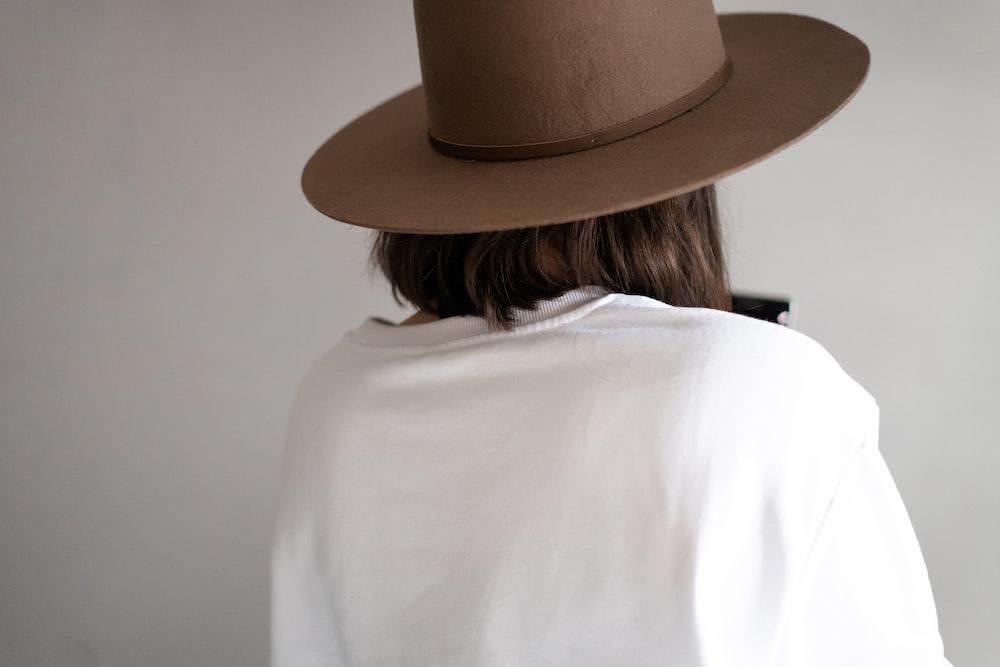 woman in white shirt wearing brown fedora hat