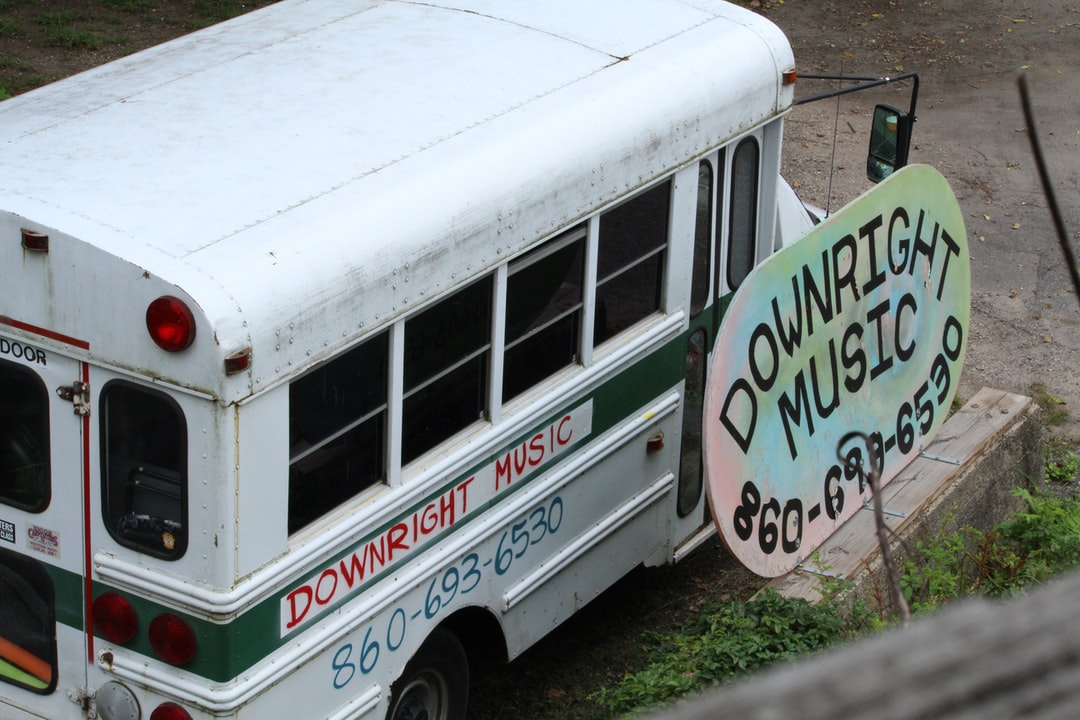 A bus advertising Downright Music in on a dirt road.