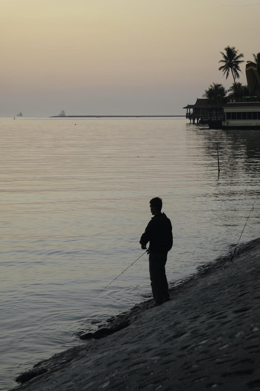 man in black jacket fishing on sea during daytime