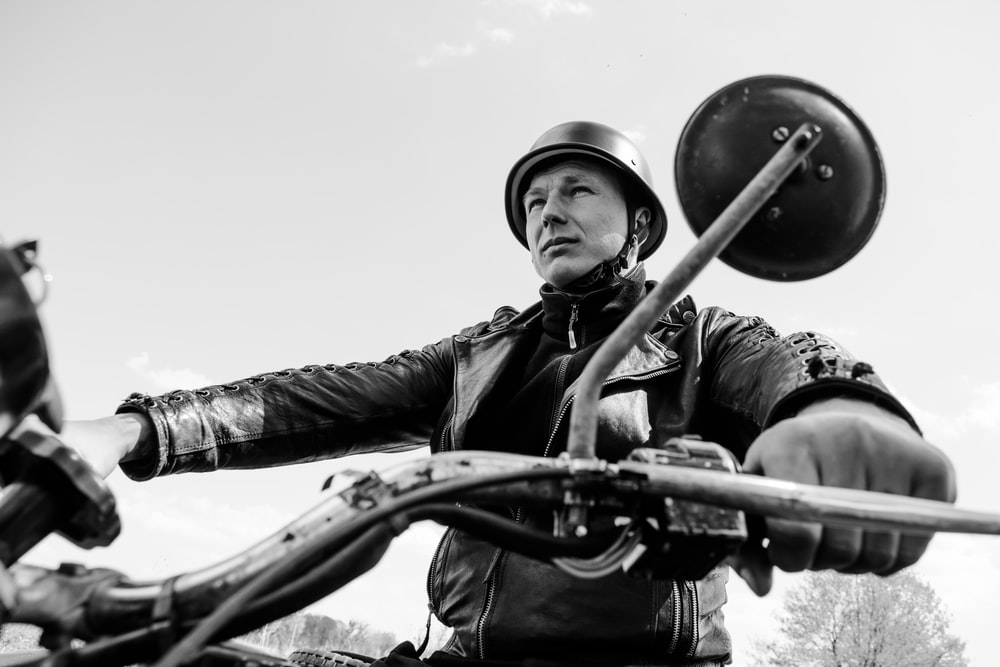 grayscale photo of man in black jacket and helmet holding rifle