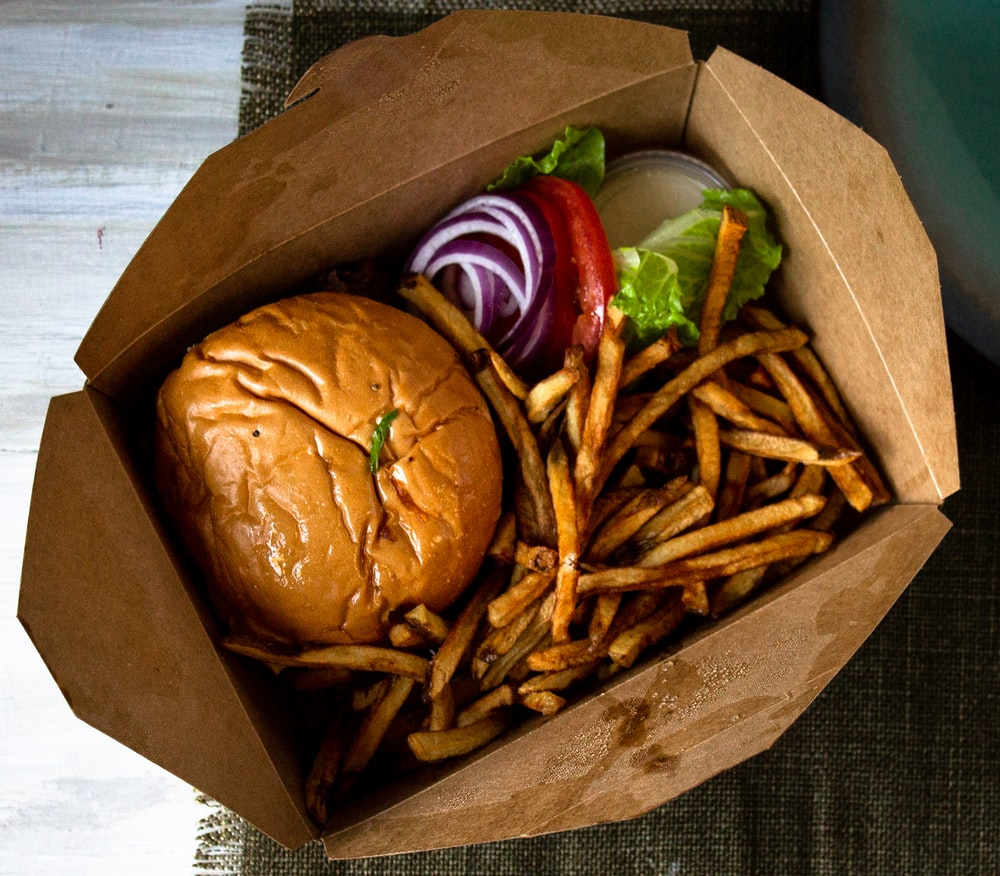 burger and fries on brown paper bag